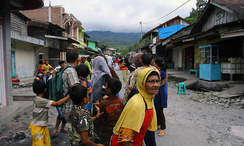 Frightened Acehnese residents gather outside their homes after a quake shook Lampahan village in Aceh province on July 2, 2013. — Photo by AFP