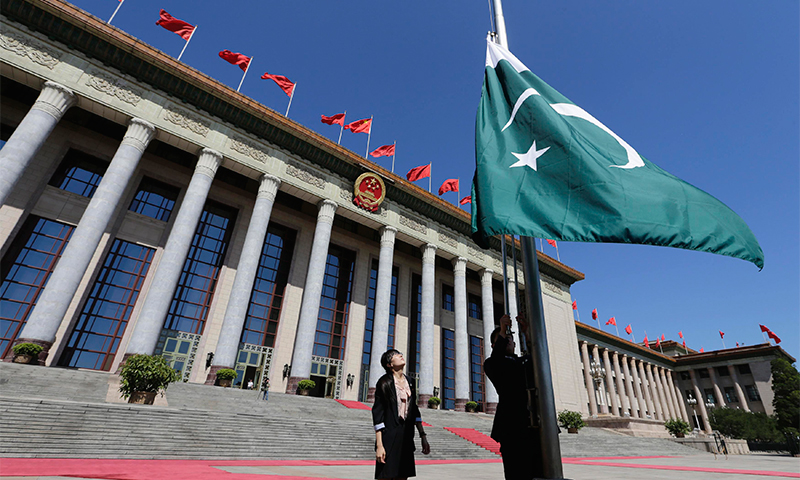 A Pakistan flag is raised aloft outside the Great Hall of the People in Beijing — Reuters