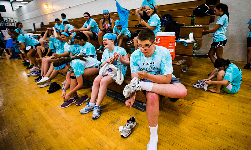 Nicholas Walker ties his shoes after participating in judo at Camp Abilities in Brockport, New York.