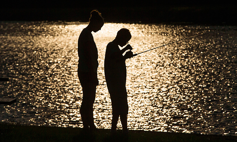 A child fishes with his counselor at Camp Abilities in Brockport, New York.