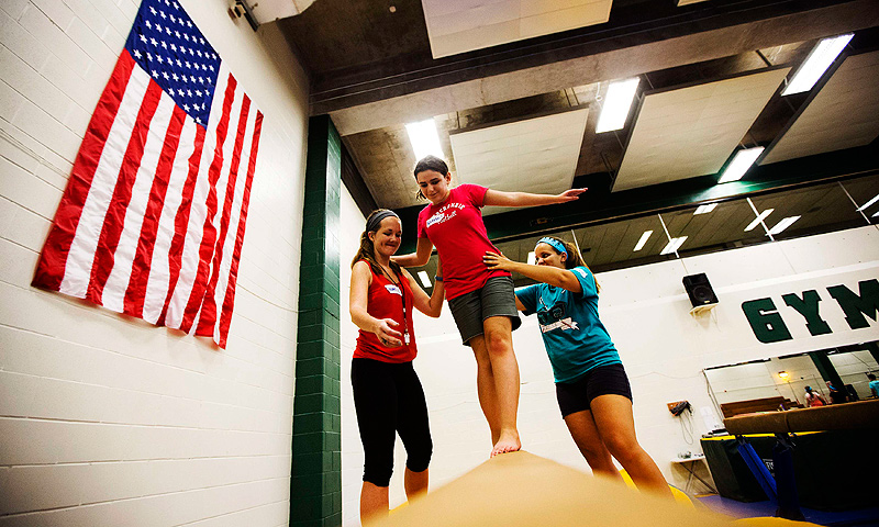 Katelin Sweeney (C) learns to walk the balance beam with assistance from counselors Lauren Allen (L) and Andrea Ayala at Camp Abilities in Brockport, New York.
