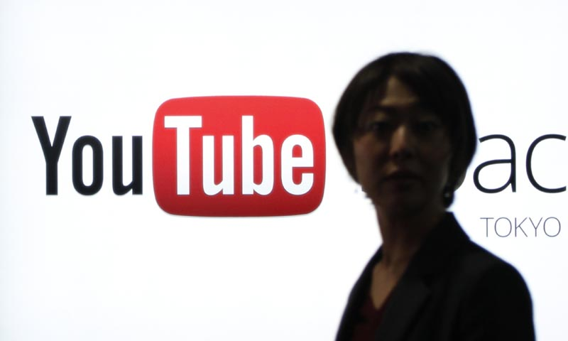 A woman walks in front of a logo of YouTube at the YouTube Space Tokyo, operated by Google, in Tokyo February 14, 2013. — Reuters Photo