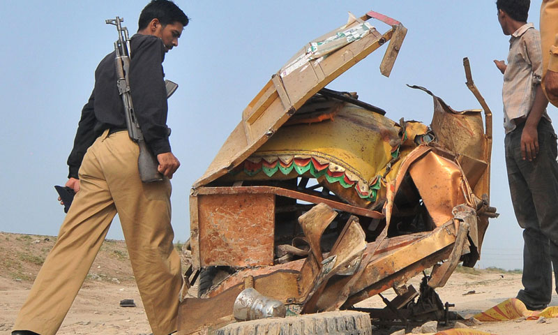 A policeman walks past the mangled wreckage of the motorcycle rickshaw after a train collided with the vehicle in Khanpur, district Sheikhupura on July 6, 2013.—AFP Photo