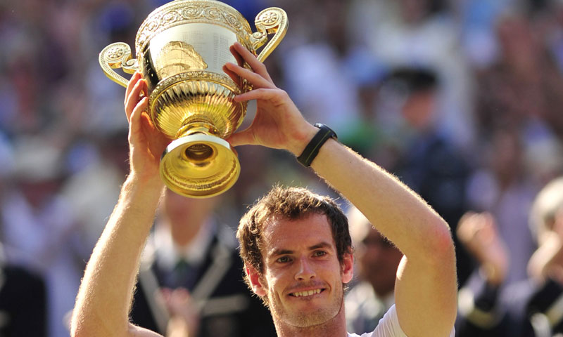 Britain's Andy Murray raises the winner's trophy after beating Serbia's Novak Djokovic in the men's singles final at Wimbledon, southwest London, on July 7, 2013. – AFP Photo