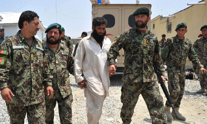 Afghanistan National Army (ANA) soldiers walk with an arrested Taliban fighter (C) at an army station on the outskirts of Jalalabad on July 7, 2013. – AFP Photo