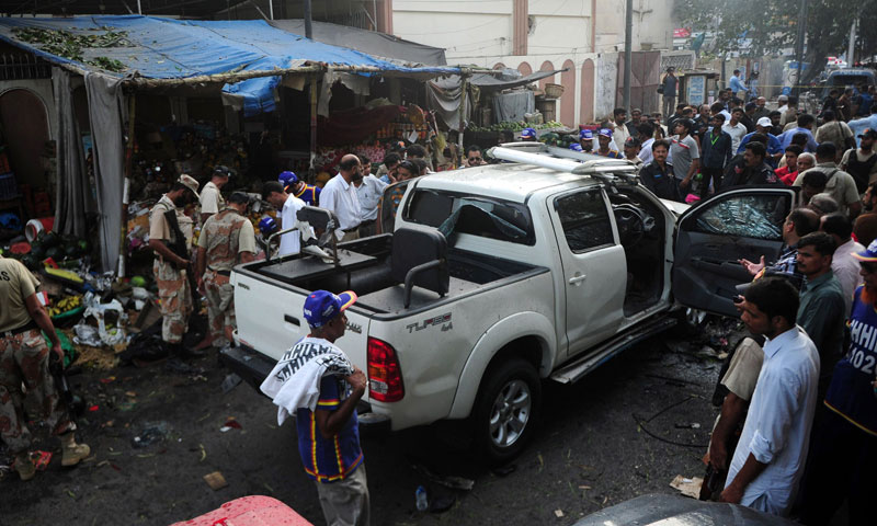 Paramilitary soldiers escort a damaged vehicle at the site of a bomb blast in Karachi on July 10, 2013. —AFP Photo