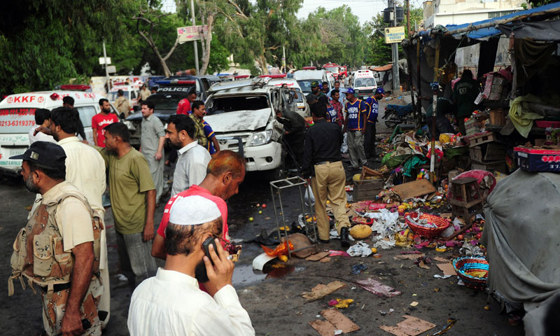 Security officials examine the site of a bomb blast in Karachi on July 10, 2013.—AFP Photo