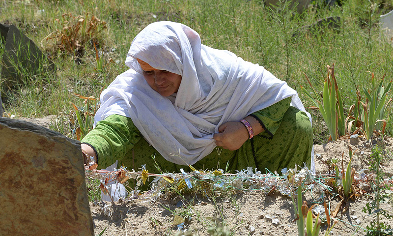 Jan Bano sits at her daughter's grave at Akhun Baba. -Photo by AFP