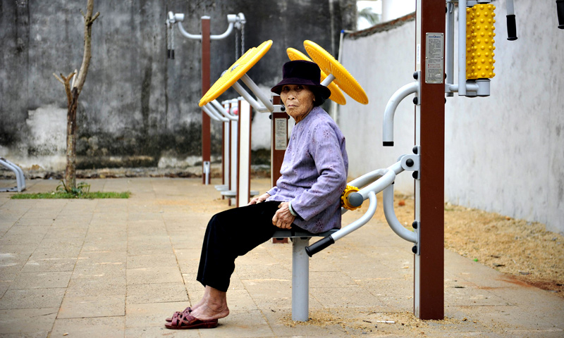 An elderly woman sitting on an exercise equipment  in Chengmai city.