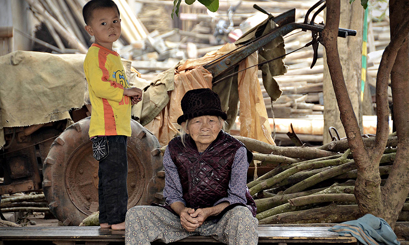 An elderly woman looking on as she having a rest with a boy by a road in Chengmai city.