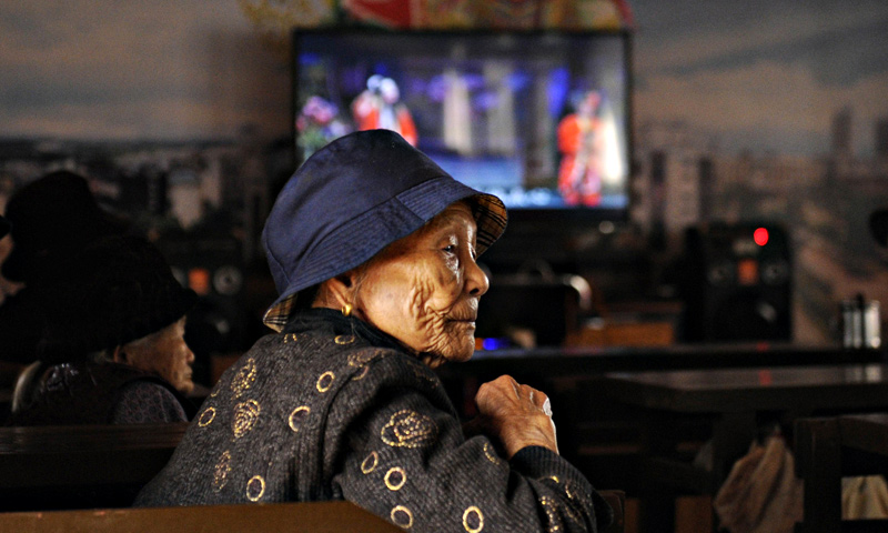 An elderly woman looking on at a tea house in Chengmai city.