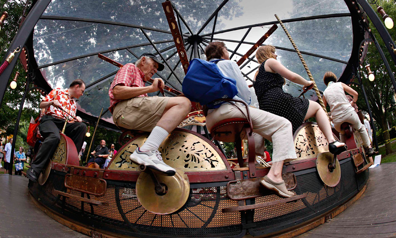 "People try out a Bicycle Carousel from the late 19th century during a media preview of ""Fete Paradiso"". — Reuters Photo"