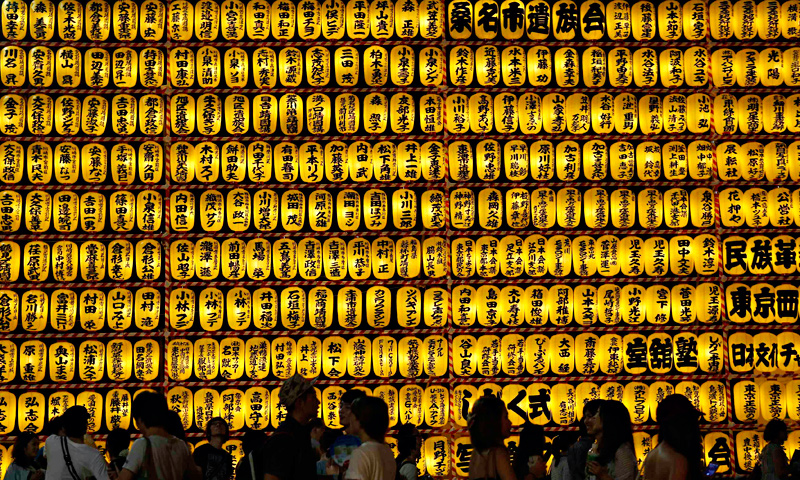 People walk in front of paper lanterns during the Mitama Festival at the Yasukuni Shrine in Tokyo, July 13, 2013.
