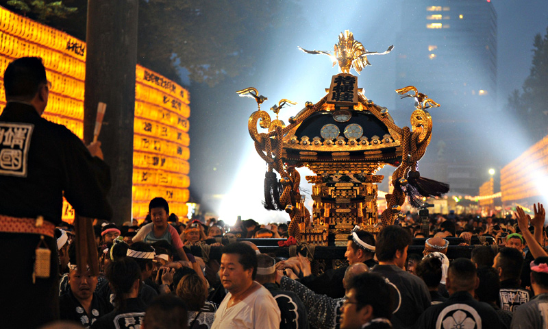 A portable shrine is carried amongst rows of lit lanterns during the Mitama Matsuri festival at the Yasukuni.  — AFP Photo