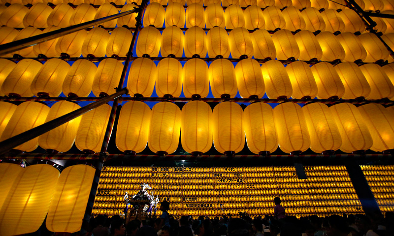 People carry a portable shrine among paper lanterns during the Mitama Festival at the Yasukuni Shrine in Tokyo, July 13, 2013.