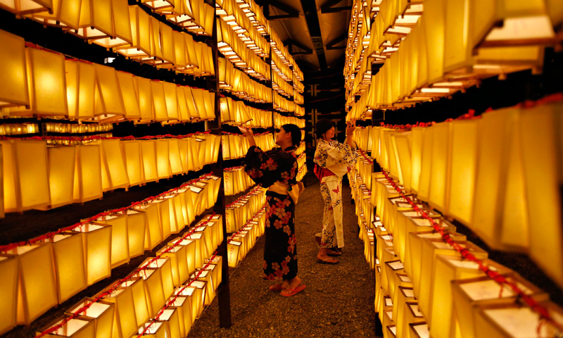 Women in yukatas, or casual summer kimonos, look at paper lanterns during the Mitama Festival at the Yasukuni Shrine in Tokyo.