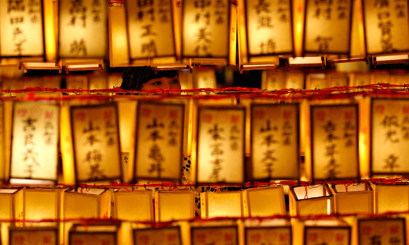A woman looks at paper lanterns during the Mitama Festival at the Yasukuni Shrine in Tokyo, July 13, 2013.