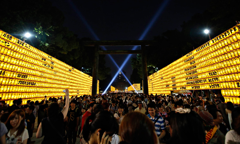 People walk among paper lanterns during the Mitama Festival at the Yasukuni Shrine in Tokyo, July 13, 2013.