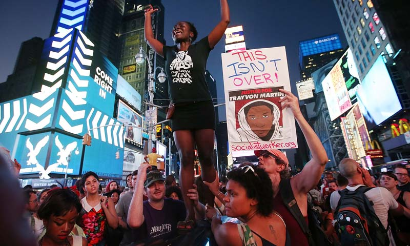 Trayvon Martin supporters rally in Times Square while blocking traffic after marching from a rally for Martin in Union Square in Manhattan on July 14, 2013 in New York City. — Photo AFP