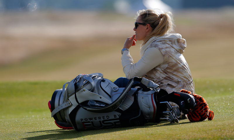 Tiger Woods' girlfriend sits near her boyfriend's golf bag.