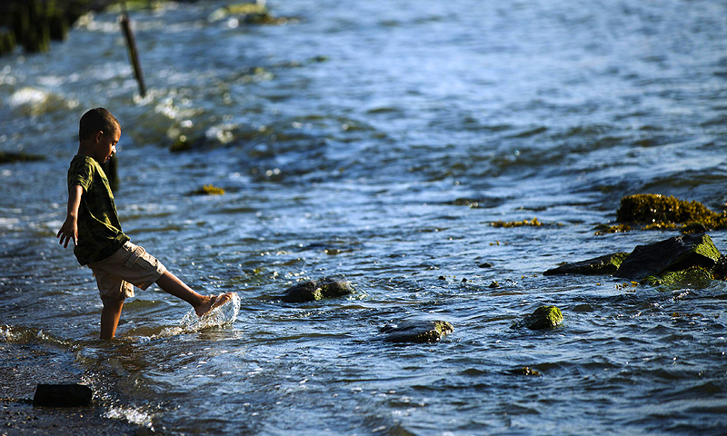 A young boy kicks water as he stands on the banks of the East River in New York. The National Weather Service issued heat advisories for dozens of northeastern cities and surrounding areas in Connecticut, Massachusetts, Rhode Island, upstate New York and Long Island.—Photo by Reuters