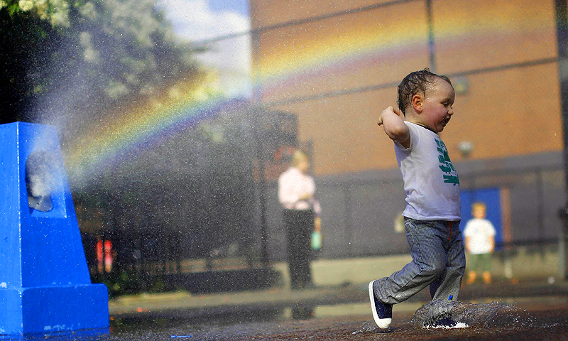 A young boy cools off in the water from a playground sprinkler in the Brooklyn borough of New York. Temperatures are set to top out in the mid-90s degrees Fahrenheit (35 degrees Celsius) through Thursday in New York City, Philadelphia and Washington, DC, with heat index values that measure humidity reaching into the upper-90s and low-100s—Photo by Reuters