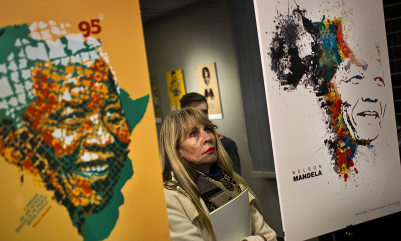 A visitor observes posters at the opening of an international exhibition of 95 posters from around the world celebrating the 95 years of the life of Nelson Mandela, at the University of Pretoria, in Pretoria, South Africa. — AP Photo