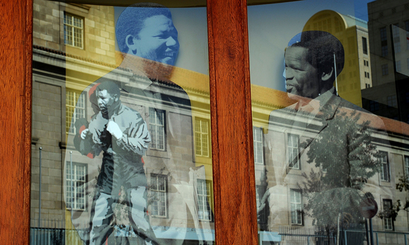 A reflection of a statue of Mandela as a boxer is seen on a building where portraits of him and Oliver Tambo (former African National Congress President) stand tall. — AFP Photo
