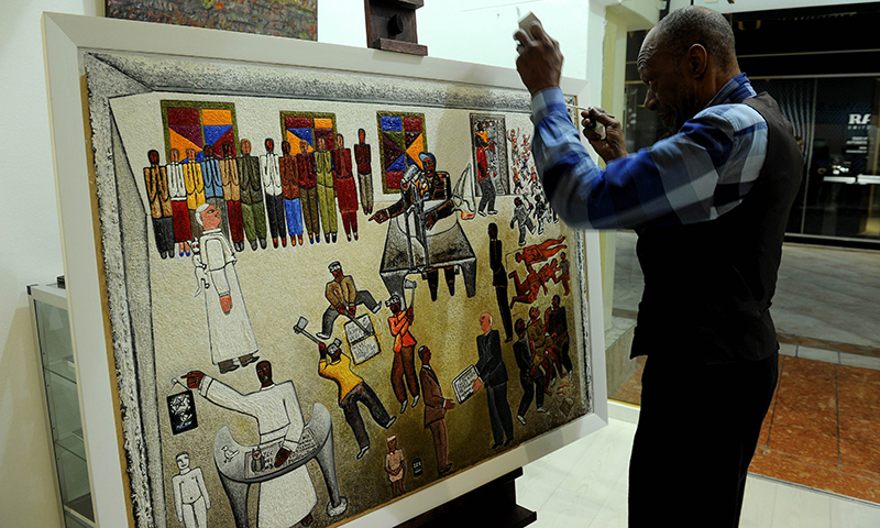 "South African artist Alfred Thoba fixes his painting, called ""Mandela and The Constitution"". — AFP Photo"