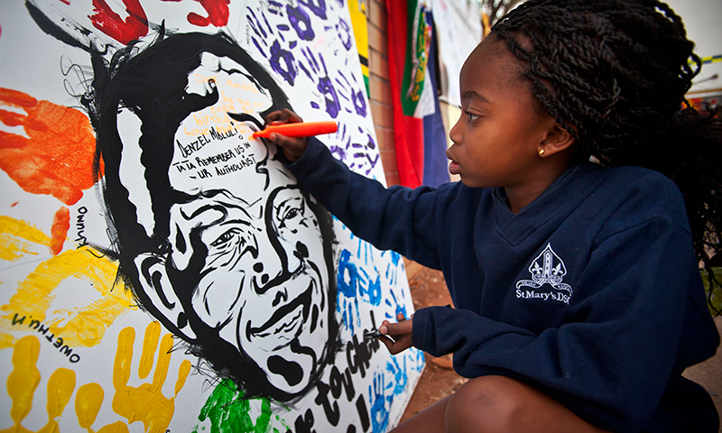 A girl writes a get-well message on a painting of Mandela outside the hospital where he's being held. — AP Photo