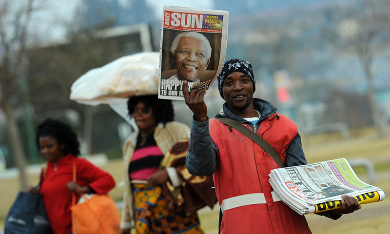A newspaper vendor show's the front page of the Daily Sun in Soweto. — AFP Photo