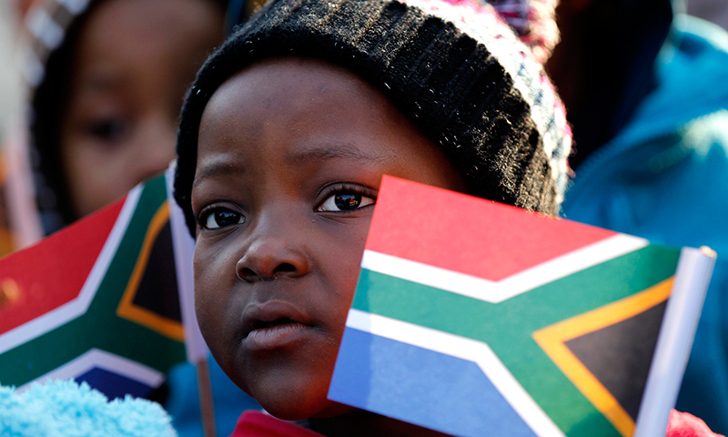 Children hold flags as they gather to wish Nelson Mandela happy birthday in Pretoria. — Reuters