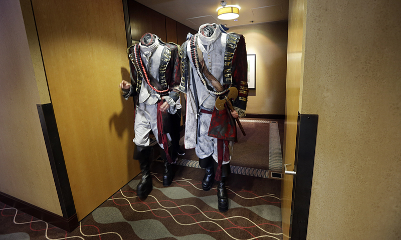 Two men dressed as headless characters get off a hotel elevator during Comic-Con.—Photo by AP