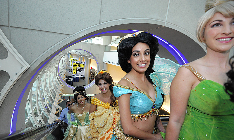 Fans dressed as Disney princesses ride the escalator as they get their credentials during the Preview Night event on Day 1 of the 2013 Comic-Con International Convention.—Photo by AP