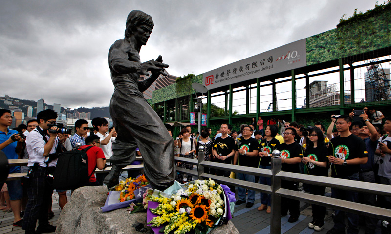 Fans pay tribute in front of the bronze statue of the late Hong Kong Kung Fu star Bruce Lee in Hong Kong Saturday, July 20, 2013 to commemorate the 40th anniversary of the death of Lee.