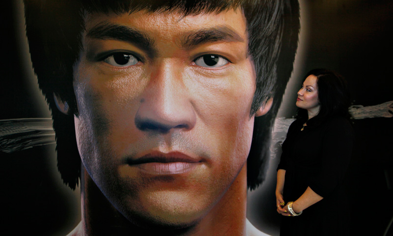 Shannon Lee, daughter of the late Kung Fu star Bruce Lee, poses in front of a promotional poster for Lee's memorial exhibition.