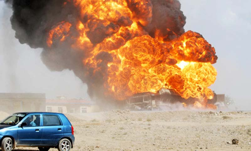 A Pakistani commuter drives past a burning oil tanker on the outskirts of Quetta.   — File Photo by AFP
