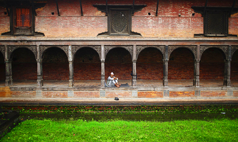 A man rests on the premises of Pashupatinath temple as he watches devotees passing by during the Shrawan Sombar festival in Kathmandu. July 22, 2013.—Photo by Reuters