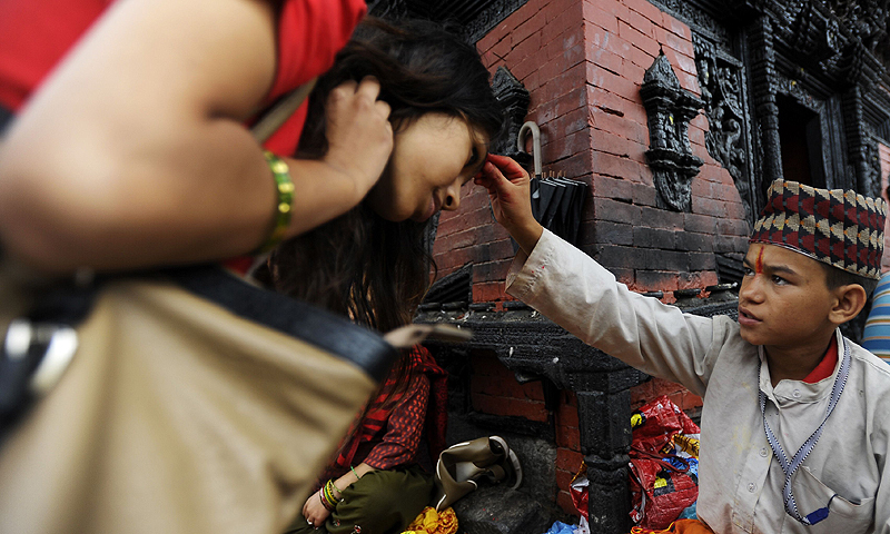 A young Nepalese Hindu priest offers tika blessings to Hindu devotees at The Pashupatinath Temple in Kathmandu.—Photo by AFP