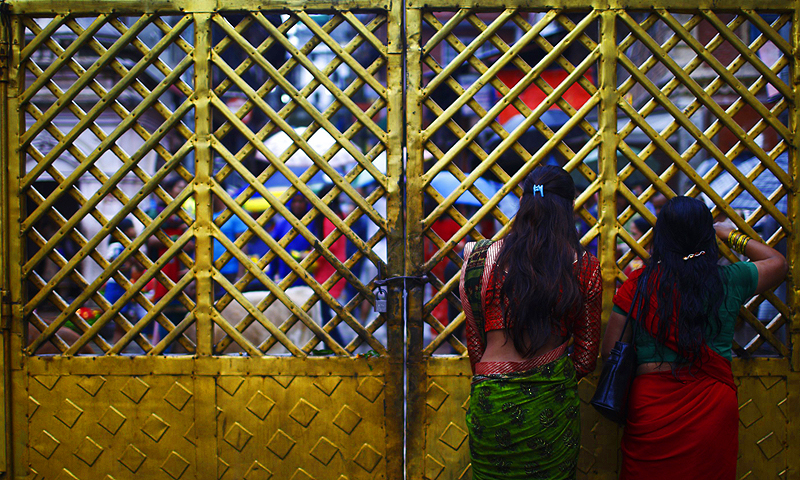 Women look out from behind a closed door at Pashupatinath temple during the Shrawan Sombar festival in Kathmandu.—Photo by Reuters