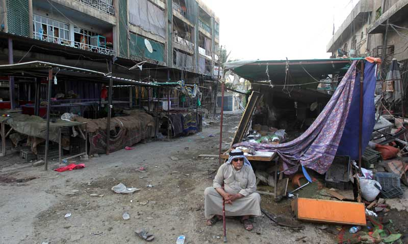 An Iraqi man sits at the site of a car bomb attack at a marketplace. — Photo by AFP/File
