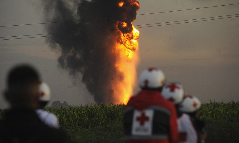 Members of the Red Cross look at an explosion of a Pemex oil pipeline in Tonanitla, near Mexico City. At least seven people were injured by an explosion after an attempt to illegally tap a pipeline belonging to the Mexican state oil monopoly Pemex near Mexico City, officials said on Sunday. The early morning blast at the crude oil pipeline occurred in Tonanitla about 40 km (25 miles) north of the capital, and was now under control, Pemex said on its Twitter account.—Photo by Reuters