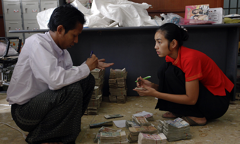 Workers count kyat banknotes at the office of a local bank in Yangon. Myanmar's government has signalled it could let foreign banks buy stakes in local lenders as it worries that resistance by domestic banks to joint ventures could hamper plans to attract investment and rebuild the financial system.—Photo by Reuters