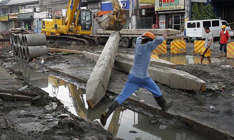 "Labourers work on ongoing road repairs along a main street at Mandaluyong city, metro Manila. The Philippines, the former ""sick man"" of Asia, has fortified its economy, positioning it to weather storms engulfing the region's vulnerable emerging markets and to snap back faster when global growth recovers.—Photo by Reuters"