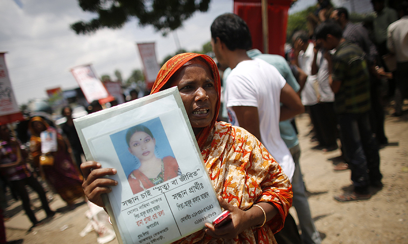 A woman holds a photograph of her relative, a garment worker who is still missing after the collapse of the Rana Plaza building, as she and others take part in a protest in front of the head office of Bangladesh Garment Manufactures & Exporters Association (BGMEA) in Dhaka July 21, 2013. Activists of Garments Sramik Sangram Parisad, a workers' rights movement, staged a protest demanding the fast payment of compensation for the Rana Plaza victims and to increase the minimum wage of all garments workers, local media