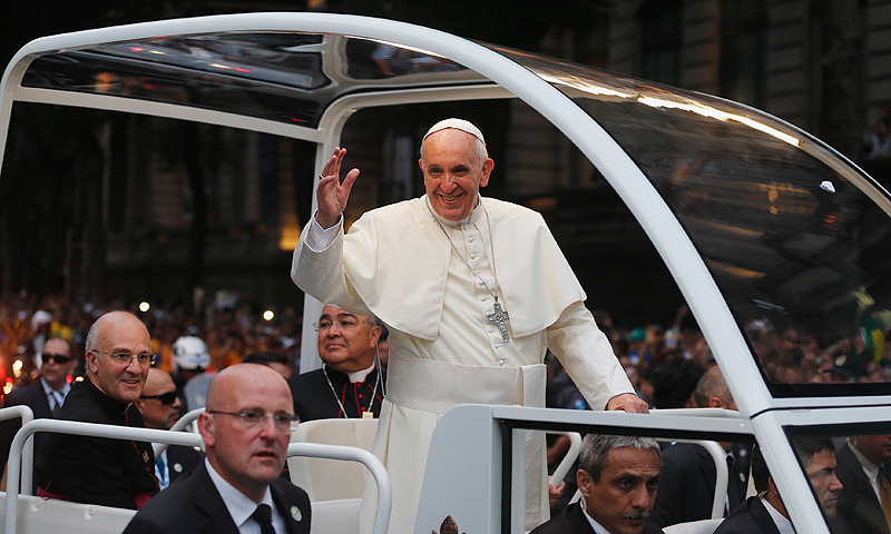 Pope Francis greets the crowd of faithful from his popemobile in downtown Rio de Janeiro. — Reuters Photo