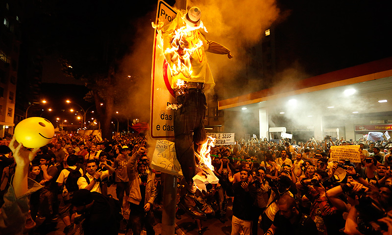Protesters burn a puppet that symbolizes Rio de Janeiro State Governor Sergio Cabral during a demonstration near Guanabara Palace in Rio de Janeiro, Brazil, Monday, July 22, 2013. — AP Photo