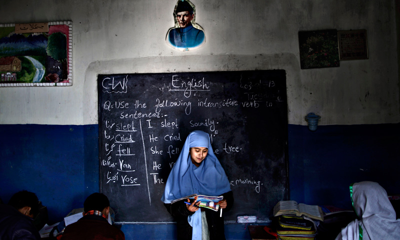 Sadia Mukhteya, 12, who was displaced with her family from Pakistan's tribal areas due to fighting between militants and the army, reads in front of the class during an English language class at a school on the outskirts of Islamabad.