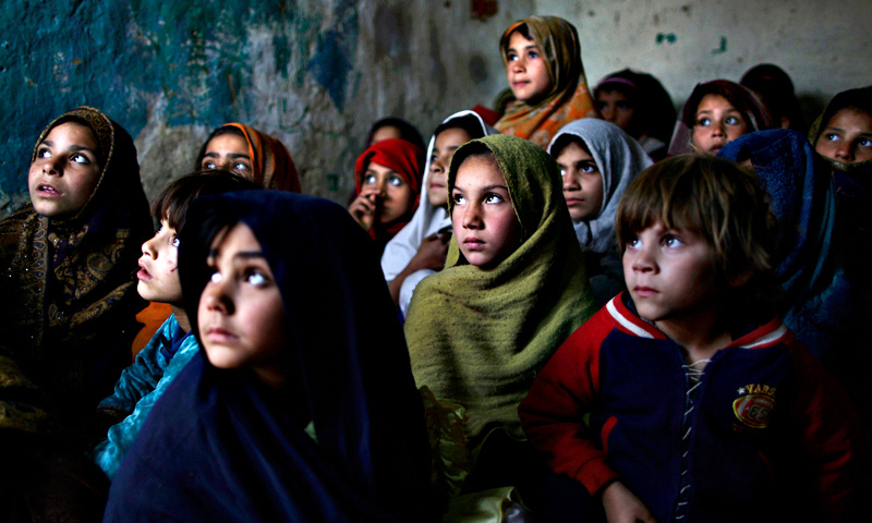 Pakistani schoolgirls, who were displaced with their families from Pakistan's tribal areas due to fighting between militants and the army, listen to their teacher, not seen, while a health worker visiting their school to give  polio vaccines, in a poor neighborhood on the outskirts of Islamabad.