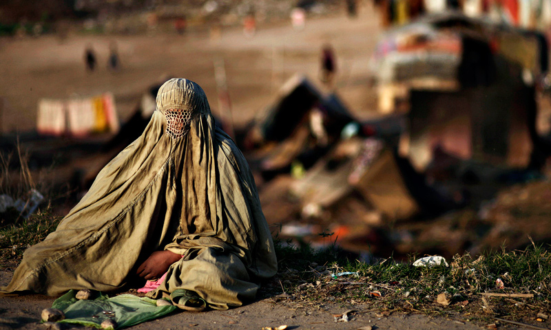 A woman sits on a roadside begging for money, in Rawalpindi.